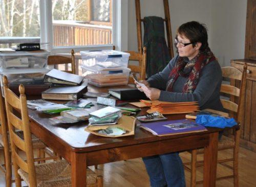 Meg Macintyre at table organizing photos